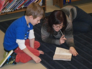 Marissa helping an elementary student in the library.